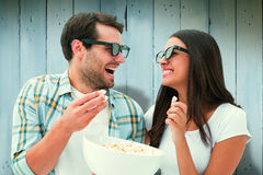 Composite image of attractive young couple watching a 3d movie Royalty Free Stock Image