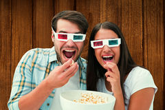 Composite image of attractive young couple watching a 3d movie Stock Photography