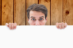 Composite image of attractive young man smiling and holding poster Stock Images