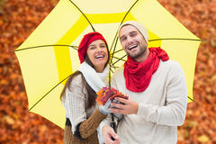 Composite image of autumn couple holding umbrella Royalty Free Stock Image