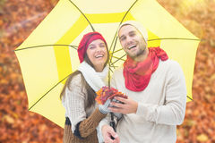 Composite image of autumn couple holding umbrella Royalty Free Stock Photos