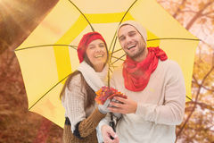 Composite image of autumn couple holding umbrella Royalty Free Stock Images