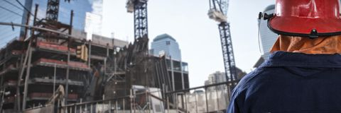Composite image of back of firefighter. Back of Firefighter against low angle view of cranes by buildings Stock Photos