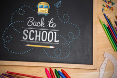 Composite image of back to school. Back to school against chalkboard on desk Royalty Free Stock Images