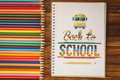 Composite image of back to school. Back to school against notepad on student desk Royalty Free Stock Image