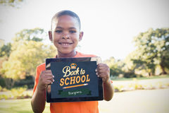 Composite image of back to school. Back to school against portrait of boy smiling while holding digital tablet Stock Photos