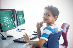 Composite image of back to school. Back to school against smiling boy using computer Royalty Free Stock Images