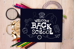 Composite image of back to school. Back to school against students desk with black page Stock Image