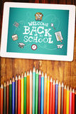 Composite image of back to school. Back to school against students desk with tablet pc Stock Image
