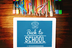 Composite image of back to school. Back to school against students desk with tablet pc Stock Photography