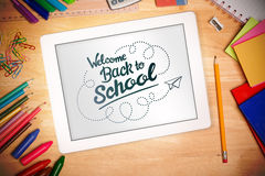 Composite image of back to school. Back to school against students desk with tablet pc Royalty Free Stock Images