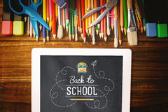Composite image of back to school. Back to school against students desk with tablet pc Royalty Free Stock Photos