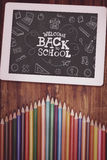Composite image of back to school. Back to school against students desk with tablet pc Royalty Free Stock Photo
