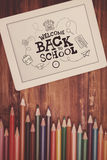 Composite image of back to school. Back to school against students desk with tablet pc Royalty Free Stock Image