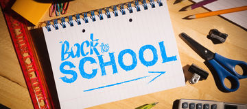 Composite image of back to school. Back to school against students table with school supplies Stock Photo