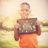 Composite image of back to school. Back to school against young boy holding digital tablet Stock Image