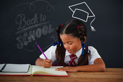 Composite image of back to school. Back to school against schoolgirl doing her homework against chalkboard Stock Image