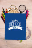 Composite image of back to school deals message. Back to school deals message against students desk with blue page Royalty Free Stock Photo