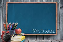 Composite image of back to school message. Back to school message against blackboard with copy space on wooden board Stock Photo