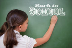Composite image of back to school message. Against cute pupil writing on chalkboard Royalty Free Stock Image