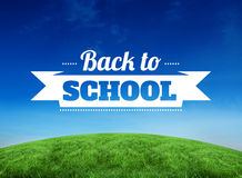 Composite image of back to school message. Back to school message against green hill under blue sky Stock Photo