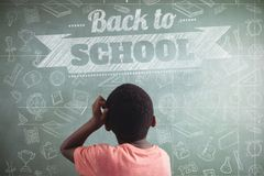 Composite image of back to school message. Back to school message against rear view of thoughtful boy against greenboard royalty free stock images