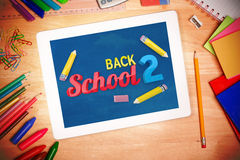 Composite image of back to school message. Back to school message against students desk with tablet pc Royalty Free Stock Photos