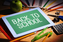 Composite image of back to school message. Back to school message against students table with school supplies Royalty Free Stock Photography