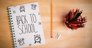 Composite image of back to school message with alarms. Back to school message with alarms against students desk royalty free stock photo