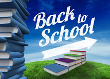 Composite image of back to school message with arrow. Back to school message with arrow against green hill under blue sky Stock Images