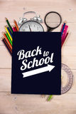 Composite image of back to school message with arrow. Back to school message with arrow against students desk with black page Royalty Free Stock Photos