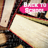 Composite image of back to school message. Back to school message against close-up of books arranged Royalty Free Stock Photo