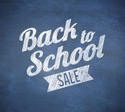 Composite image of back to school sale message. Against blue chalkboard Royalty Free Stock Photo