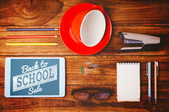 Composite image of back to school sale message. Back to school sale message against tablet next to cup and notepad Stock Photos