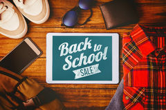 Composite image of back to school sale message. Back to school sale message against tablet shirt jean shoes smartphone wallet and bag Stock Photo