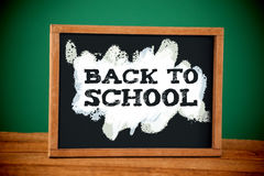 Composite image of back to school text on green and blue splash. Back to school text on green and blue splash against empty blackboard on wooden table Stock Images
