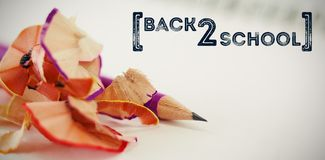 Composite image of back to school text over white background. Back to school text over white background against close-up of pencil with shavings Stock Photo