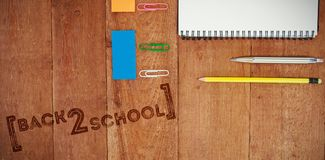 Composite image of back to school text over white background. Back to school text over white background against overhead view of pencil and book on table Royalty Free Stock Photo