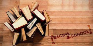 Composite image of back to school text over white background. Back to school text over white background against various type of books arranged Royalty Free Stock Images