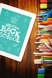 Composite image of back to school written on chalkboard. Back to school written on chalkboard against students desk with tablet pc Stock Photos