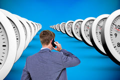 Composite image of back turned businessman on the phone. Back turned businessman on the phone against blue background with vignette Stock Image