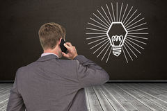 Composite image of back turned businessman on the phone Royalty Free Stock Images