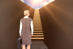 Composite image of back turned businesswoman holding a briefcase 3d. Back turned businesswoman holding a briefcase against grey 3d Royalty Free Stock Photo