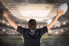Composite image of back turned rugby player gesturing victory Stock Photos