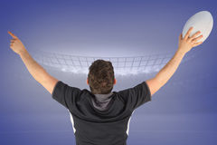 Composite image of back turned rugby player gesturing victory. Back turned rugby player gesturing victory against purple vignette Royalty Free Stock Photo