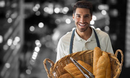 Composite image of baker holding bread in whisker basket stock image