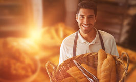 Composite image of baker holding bread in whisker basket royalty free stock photos