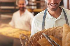 Composite image of baker holding bread in whisker basket royalty free stock images