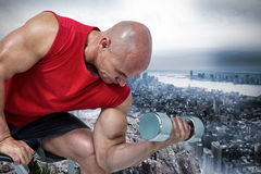 Composite image of bald man exercising with dumbbells while sitting on bench press Stock Photos