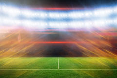 Composite image of ball of fire 3d. Ball of fire against football pitch under blue lights 3d Stock Photo